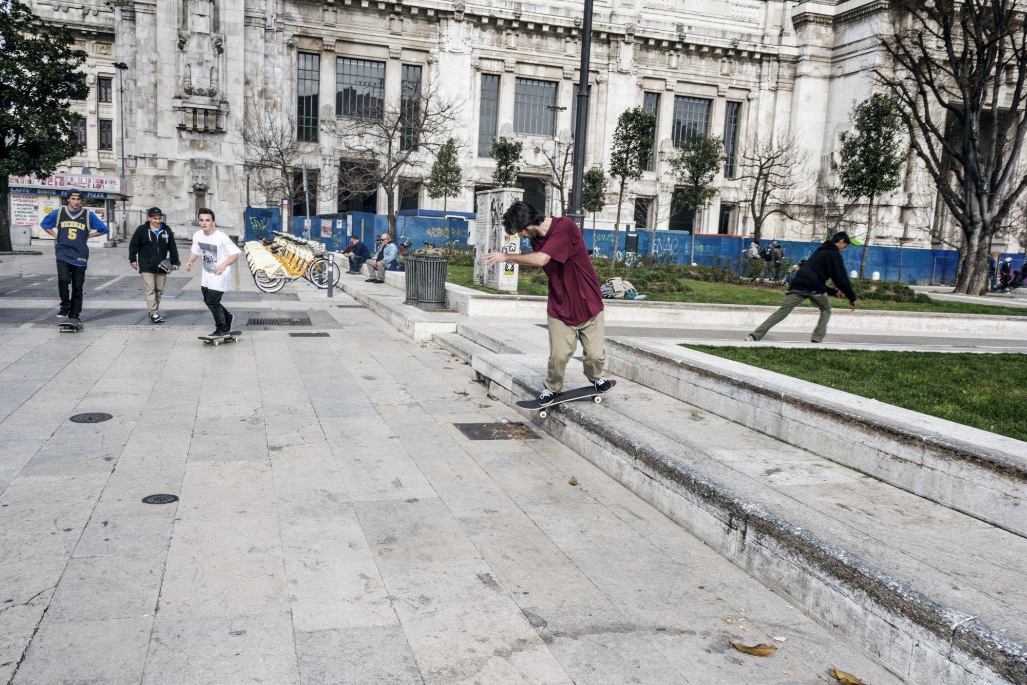 Uno skateboarder esegue un trick davanti alla Stazione Centrale di Milano